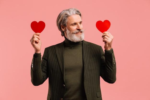 Felice uomo maturo con barba e baffi in abito color kaki con cuori rossi saluto san valentino isoleted sfondo rosa.