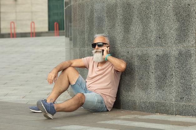 Uomo anziano barbuto felice che parla dal telefono. uomo maturo alla moda allegro che parla dallo smartphone. ritratto dell'uomo maggiore moderno che parla dal telefono all'aperto.
