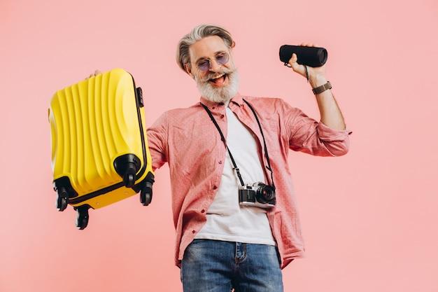 Felice uomo alla moda con la barba in occhiali da sole con la macchina fotografica che tiene una valigia e un altoparlante portatile