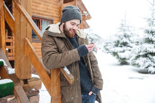 Felice giovane barbuto in piedi e utilizza lo smartphone vicino al cottage di legno in inverno