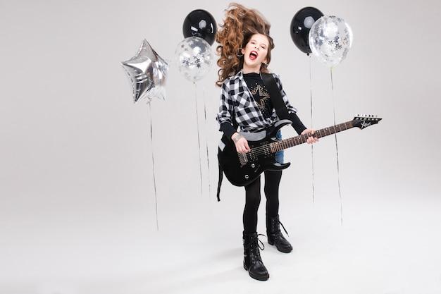 Bella piccola ragazza artistica felice che gioca chitarra