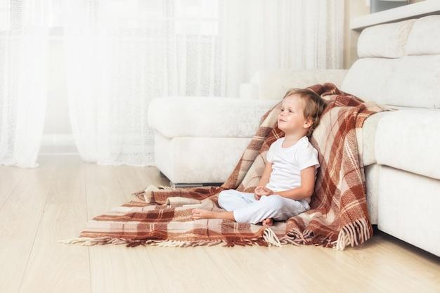 Bambino felice e bello che sorride a casa nel soggiorno seduto sul pavimento su una coperta