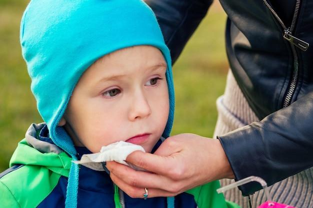 Felice e bella donna bionda in cappello che gioca pulisce le mani con i tovaglioli del figlio del bambino in una giacca calda nel parco autunnale sullo sfondo del lago. madre alla moda con un bambino