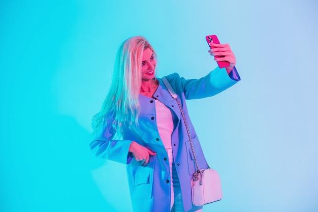 Felice bella donna bionda con un sorriso carino in abiti da lavoro di moda guarda con una borsa e un blazer fa una foto selfie sullo smartphone in studio su una luce multicolore