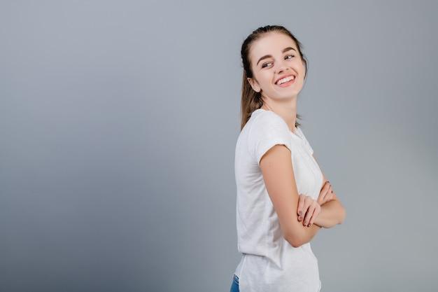 Bella donna felice del brunette con copyspace alla sua sinistra isolata sopra grey