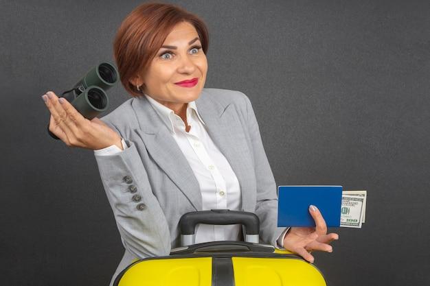 La bella donna felice di affari guarda con il binocolo in sorpresa verso il suo viaggio