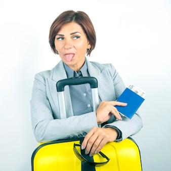 Felice bella donna d'affari con passaporto e bagagli in viaggio. vacanze e divertimento. cerca luoghi in cui viaggiare. mostra la lingua.