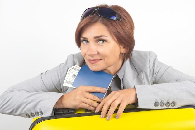 Felice bella donna d'affari con passaporto e bagagli in viaggio. vacanze e divertimento. cerca luoghi in cui viaggiare.