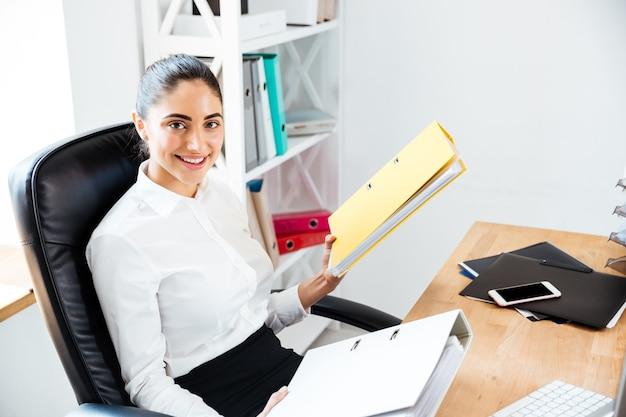 Felice bella donna d'affari che tiene i raccoglitori e guarda davanti mentre è seduta in ufficio