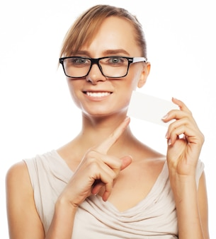 Felice bella donna d'affari con gli occhiali in possesso di un biglietto vuoto