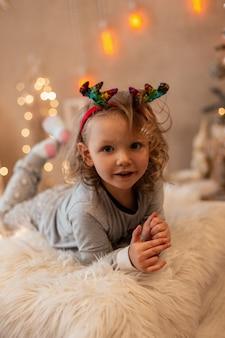 La bella bambina felice si trova sul letto su uno sfondo di decorazioni e luci natalizie. vacanze invernali