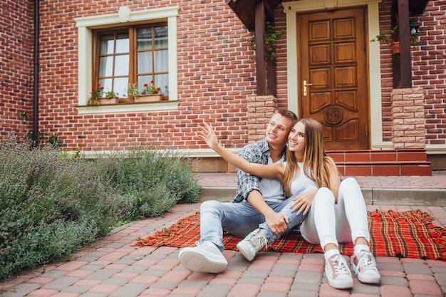 Belle coppie felici che si siedono al tappeto della coperta davanti alla nuova casa