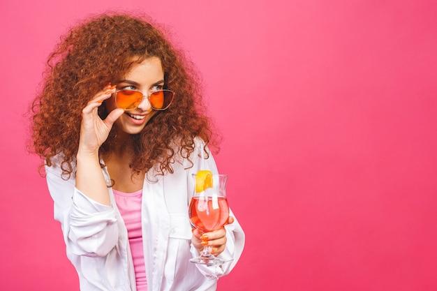 Felice bella donna riccia in abiti casual estivi con un bicchiere di cocktail