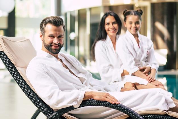 La bella famiglia felice in accappatoio è gioiosa insieme mentre era seduto nel salone della stazione termale