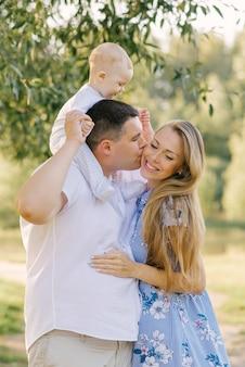 Felice bella famiglia. il papà grasso tiene il suo piccolo figlio al collo e bacia la sua bellissima moglie, che lo abbraccia e sorride