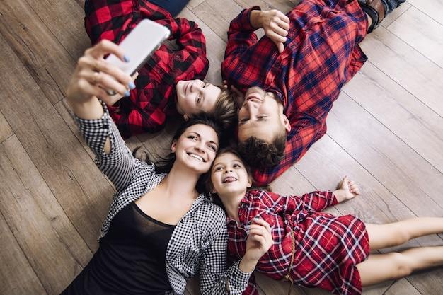 Felice bella famiglia felice rendendo selfie sul telefono cellulare insieme a casa sdraiato sul pavimento