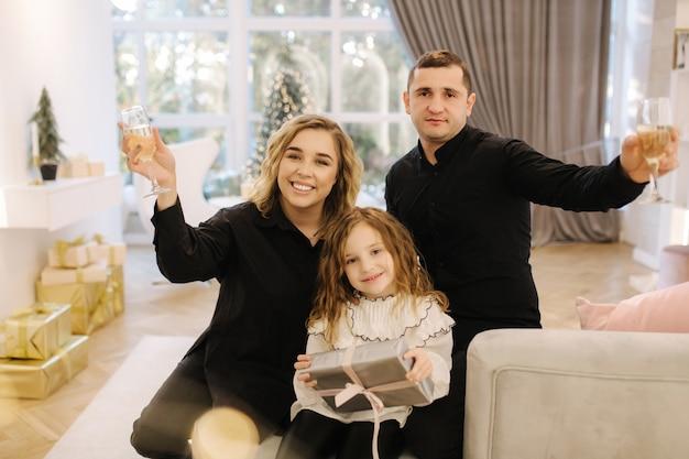 Bella famiglia felice di mamma, papà e figlia nel periodo natalizio da un bellissimo albero di natale.