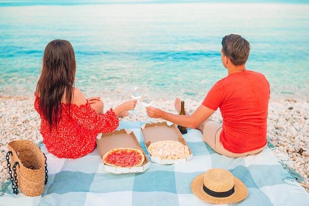 Bella famiglia felice su una spiaggia tropicale che ha picnic insieme sul tramonto