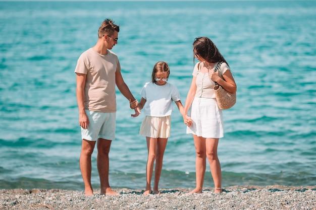 Bella famiglia felice con il bambino insieme sulla spiaggia tropicale durante le vacanze estive