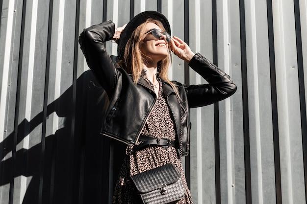 Felice bella ragazza alla moda con occhiali da sole in stile in abito vintage con giacca di pelle nera e borsa si diverte vicino a una parete di metallo