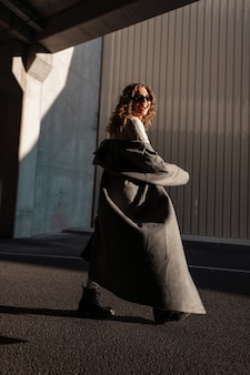 Felice bella giovane divertente con i capelli ricci donna in un cappotto lungo alla moda con occhiali da sole alla moda cammina per strada in una giornata di sole e sfumature