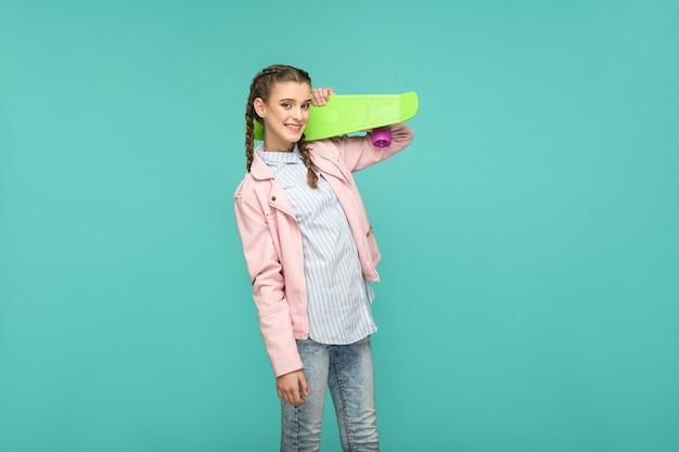 Felice bella ragazza in stile casual, capelli a codino e giacca rosa, in piedi e tenendo in mano lo skateboard e guardando la telecamera con un sorriso a trentadue denti, studio al coperto, isolato su sfondo blu o verde