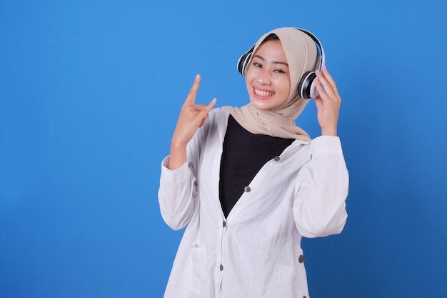 Bella ragazza felice ballare e ascoltare musica in cuffie wireless