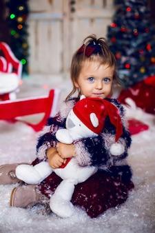 Principessa bella ragazza felice in vestito bianco che abbraccia un orsacchiotto con l'albero di natale e le luci notturne.