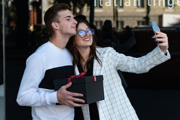 La bella ragazza felice prende un selfie con il suo ragazzo. il ragazzo fa un regalo alla ragazza. coppia felice ad un appuntamento in città.