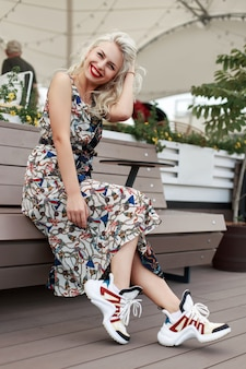 Felice bella ragazza in abito vintage con motivo e scarpe da ginnastica alla moda seduto e rilassante su una panchina in città