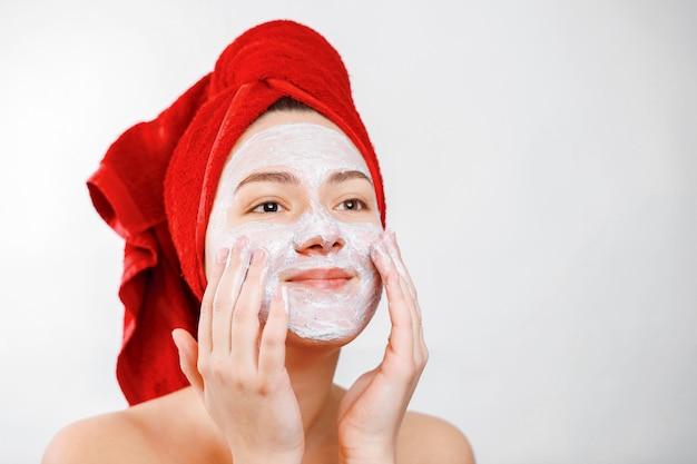 Felice bella ragazza con un asciugamano rosso in testa applica uno scrub sul viso di un grande ritratto di ruolo emotivo di genere