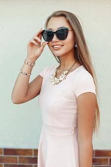Bella ragazza felice con un sorriso in occhiali da sole vicino al muro