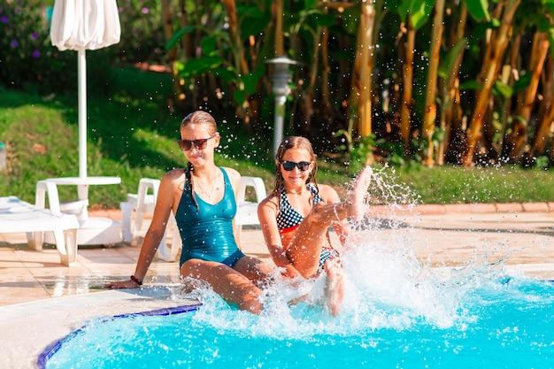 Belle ragazze felici che si divertono in piscina al resort