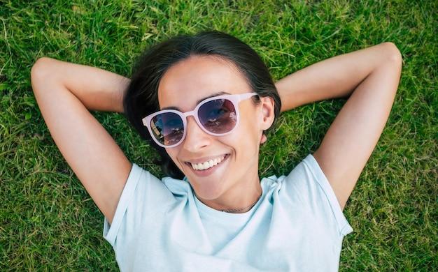 Felice bella donna hipster in occhiali da sole cool si diverte mentre è sdraiata sul prato