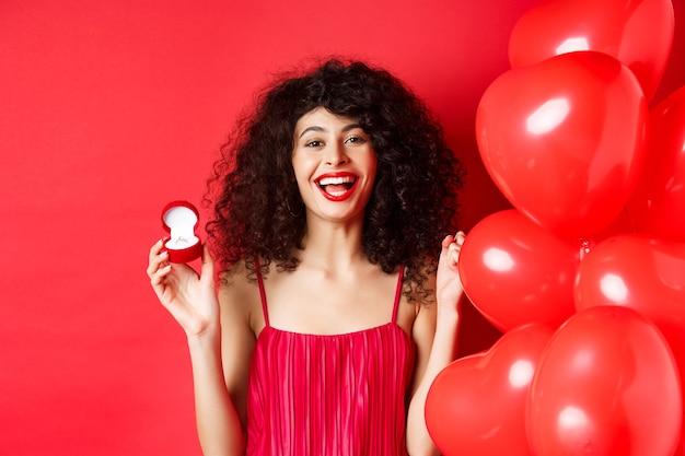 Felice bella signora che si sente eccitata per la proposta di matrimonio, mostrando l'anello di fidanzamento e ridendo, in piedi vicino a palloncini cuore su sfondo rosso.