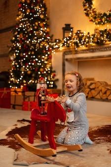 Felice bella bambina in pigiama alla moda è giocato con uno schiaccianoci e un cavallo oscillante rosso vicino al camino sullo sfondo delle decorazioni natalizie