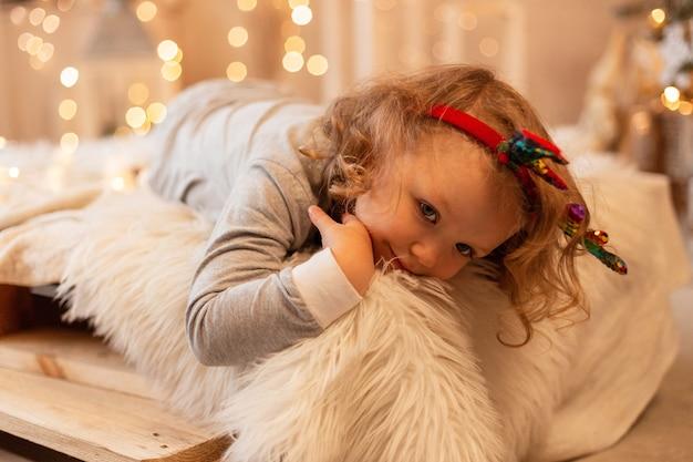 Felice bella bambina in pigiama giace sul letto sullo sfondo di luci e decorazioni natalizie.