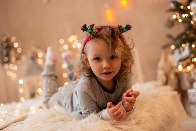 Felice bella bambina con corna di cervo di natale in pigiama alla moda sdraiato su un letto sullo sfondo delle luci