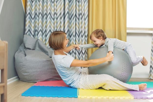 Felice e bella madre e figlio, la famiglia insieme fa l'allenamento con la palla da ginnastica