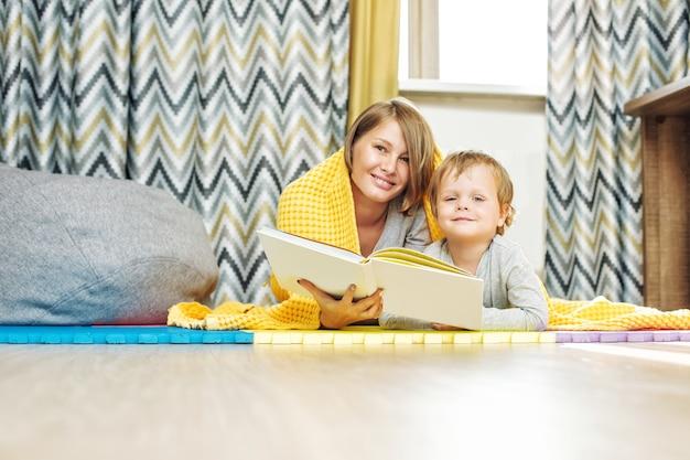 Felice e bella famiglia madre e figlio insieme leggendo un libro sdraiato nella scuola materna