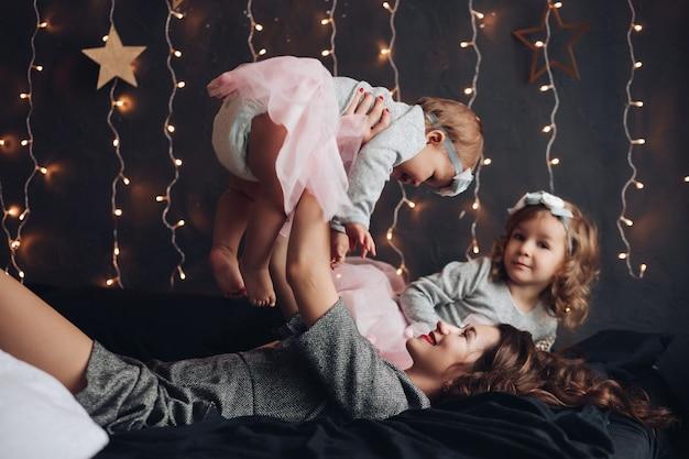 Bella madre felice che si diverte con la figlia più giovane sdraiata sul letto