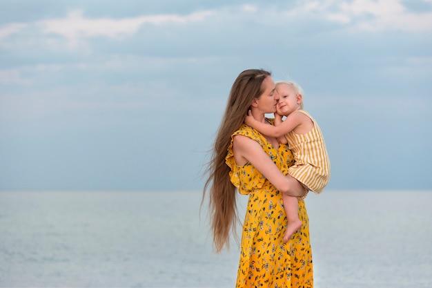 Bambino enorme felice bella madre vicino al mare. madre e figlia.