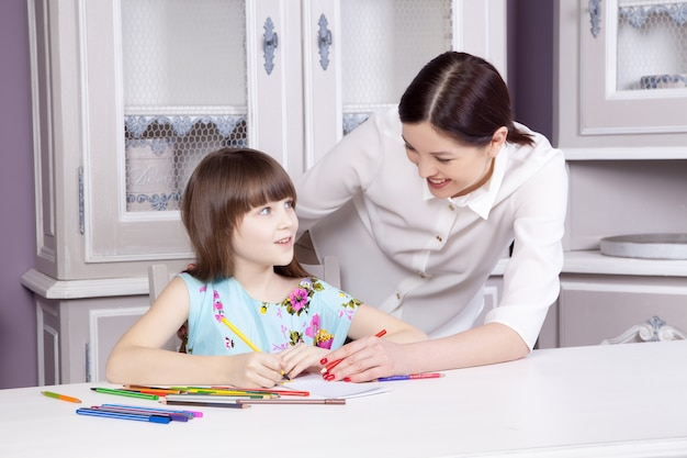La bella madre felice insegna a sua figlia a dipingere, dipingere e sorridere e guardare la macchina fotografica. colpo dello studio.