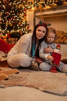 La bella madre felice con sua figlia è seduta vicino al caminetto e alle decorazioni natalizie e gioca insieme con un giocattolo. vacanze invernali in famiglia