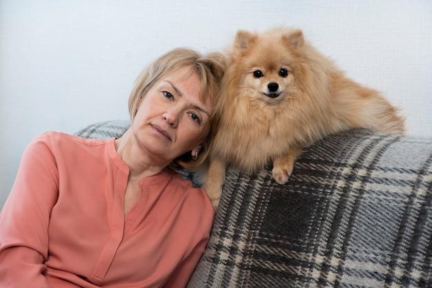 Felice bella signora positiva, donna senior anziana seduta al divano nel soggiorno di casa con lei