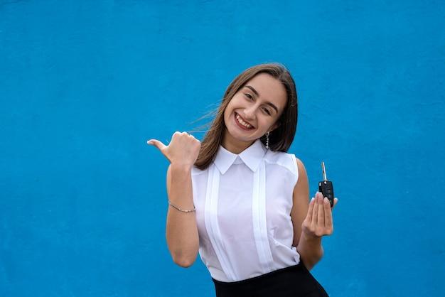 Felice bella commessa con un'auto chiavi su sfondo blu