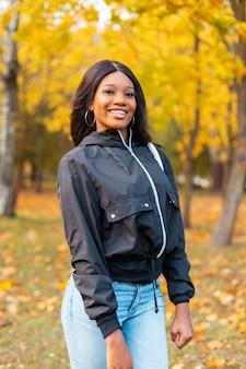 Felice bella donna afroamericana sorridente in abiti casual alla moda che cammina nel parco colorato autunnale
