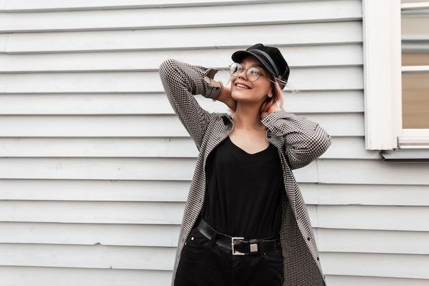 Felice bella ragazza sorridente con occhiali vintage in abiti autunnali casual alla moda si trova vicino a una casa di legno
