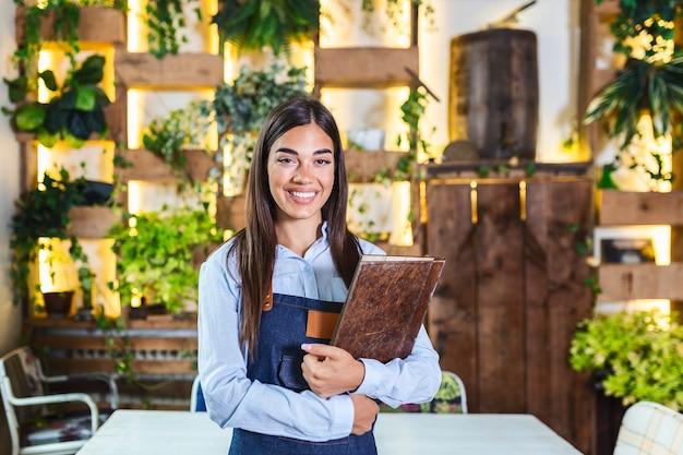 Felice bella cameriera sorridente che indossa il grembiule che tiene un menu di cartelle in un ristorante, guardando la fotocamera, in piedi in un accogliente caffè, buon servizio