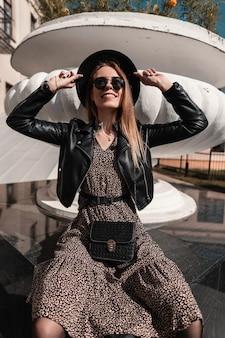 Felice bella donna sorridente con occhiali da sole e cappello alla moda in giacca di pelle nera e abito vintage con borsa alla moda si trova in città in una giornata di sole
